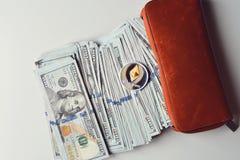 Ethereum na pilha de notas de dólar dos E.U., metade dentro de uma carteira alaranjada fotografia de stock
