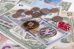 Ethereum och Litycoin mynt som ligger på euro- och dollarsedlar med röd tärning Begreppsblockchain, cryptocurrencies, investering Arkivfoton