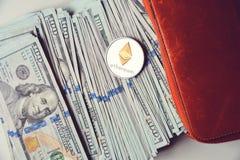 Ethereum op stapel van Amerikaanse dollarrekeningen, de helft binnen een oranje portefeuille Stock Fotografie