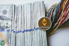 Ethereum and wires and Us 100 dollar bills. Ethereum on a pile of US 100 dollar bills and colorful wires , on a white background Royalty Free Stock Photos