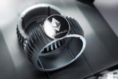 Ethereum srebna crypto moneta kłama na gearwheel zdjęcie stock