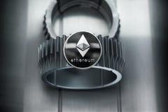 Ethereum srebna crypto moneta kłama na gearwheel obraz royalty free
