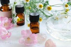Etherische oliën met kamille en roze bloemen Stock Afbeeldingen