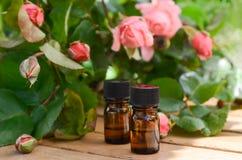 Etherische oliën met roze bloemen Stock Foto