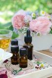 Etherische oliën met roze bloemen en thee voor aromatherapy behandeling Stock Foto