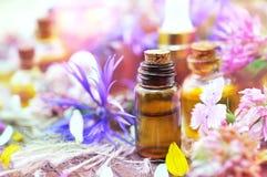 Etherische oliën op geneeskrachtige bloemen en kruidenachtergrond: kamille, klaver, duizendblad royalty-vrije stock afbeeldingen