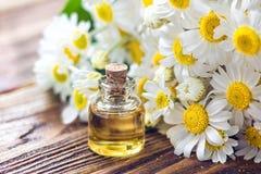 Etherische olie in glasfles met verse kamillebloemen, schoonheidsbehandeling Zeep, handdoek en bloemensneeuwklokjes Selectieve na Royalty-vrije Stock Afbeeldingen