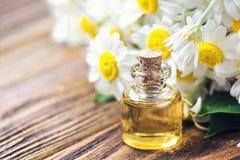 Etherische olie in glasfles met verse kamillebloemen, schoonheidsbehandeling Zeep, handdoek en bloemensneeuwklokjes Selectieve na Royalty-vrije Stock Foto's