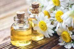Etherische olie in glasfles met verse kamillebloemen, schoonheidsbehandeling Zeep, handdoek en bloemensneeuwklokjes Selectieve na Royalty-vrije Stock Fotografie