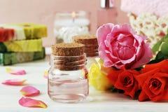 Etherische olie met roze bloemblaadjes stock afbeelding