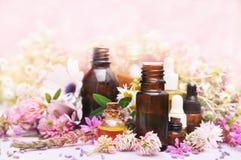 Etherische olieflessen op geneeskrachtige roze bloemen en kruidenachtergrond royalty-vrije stock afbeeldingen