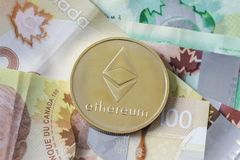 Etherium Coin on Money. A gold Etherium Token on Canadian Cash royalty free stock photography