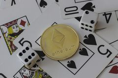 An etherium token with dice and cards.  royalty free stock image