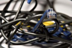 Ethernet cable (4). Coiled ethernet cable peering out of a wired mess Stock Image