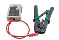 Ethernet-Kabel, Bördelmaschine und RJ45 verkabeln die Prüfvorrichtung, die auf Weiß lokalisiert wird Stockbild
