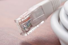 Ethernet RJ45 white Network Cable on wooden desk back. Closeup of ethernet RJ45 white Network Cable on wooden desk background Stock Photos
