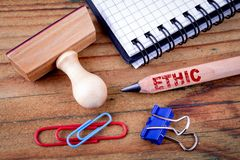 Ethic text on pencil. Stationery on an old wooden background stock photo