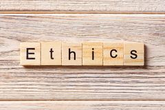 Ethics word written on wood block. Ethics text on table, concept stock image
