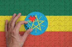Ethiopia flag is depicted on a puzzle, which the man`s hand completes to fold.  stock illustration
