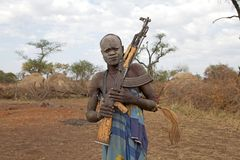 Mursi man Ethiopia. Ethiopia: Mursi man with assault rifle AK-47 with the village huts in the background. Mursi are a Nilotic pastoralist ethnic group that Stock Photo