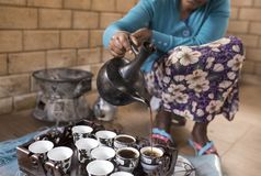 Ethiopian coffee ceremony. Closeup of Ethiopian womans hands as she pours coffee in Ethiopian coffee ceremony Stock Images