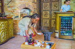 Ethiopian coffee for tourists. KIEV, UKRAINE - JUNE 4, 2017: Ethiopian Tigrayan woman performs traditional coffee ceremony, she pours coffee from jebena boiling Stock Image