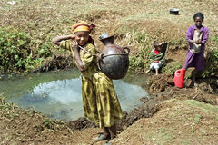 Ethiopian girls fetching water in natural water well Stock Image