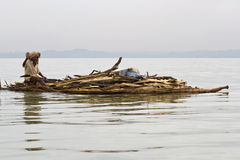 Ethiopian native transports logs on Lake Tana. LAKE TANA, ETHIOPIA - FEBRUARY 26, 2010: Unidentified Ethiopian man transports logs in a papyrus boat and waves Royalty Free Stock Images
