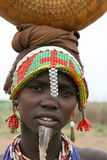 Ethiopian woman carrying goods on head. A young woman from a village near Omorate in Southern Ethiopia decorated with plastic beads and a metal hand-watch Stock Photo