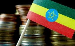 Ethiopische vlag die met stapel geldmuntstukken golven Stock Afbeelding