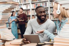 Ethnic african american guy and white girl surrounded by books in library. Students are using tablet. stock image