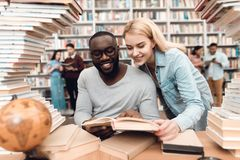 Ethnic african american guy and white girl surrounded by books in library. Students are reading book. Ethnic african american guy and white girl sitting at Stock Photo