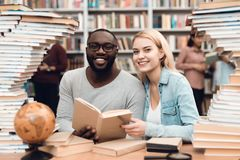 Ethnic african american guy and white girl surrounded by books in library. Students are reading book. Ethnic african american guy and white girl sitting at Stock Photos