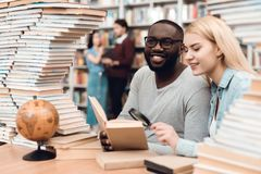 Ethnic african american guy and white girl surrounded by books in library. Students are reading book with loupe. Ethnic african american guy and white girl Stock Image