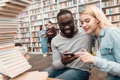 Ethnic african american guy and white girl surrounded by books in library. Students are taking selfie. stock image