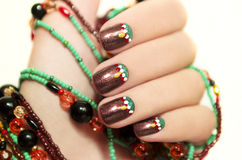 Ethnic art design. Ethnic art design of the nails on a woman s hand embellishment from beads on a white background royalty free stock photo