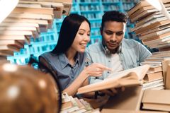 Ethnic asian girl and indian mixed race guy surrounded by books in library. Students are reading book. Ethnic asian girl and indian mixed race guy sitting at Royalty Free Stock Photos