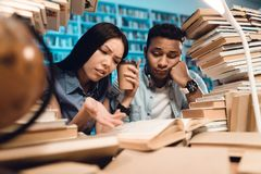 Ethnic asian girl and indian mixed race guy surrounded by books in library. Students are reading book. Ethnic asian girl and indian mixed race guy sitting at Royalty Free Stock Photo