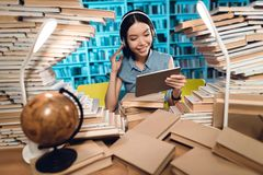 Ethnic asian girl surrounded by books in library at night. Student is listening to music on tablet. royalty free stock photo