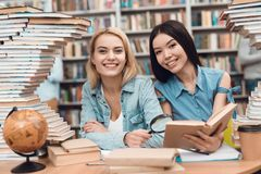 Ethnic asian girl and white girl surrounded by books in library. Students are reading book. Ethnic asian girl and white girl sitting at table surrounded by Royalty Free Stock Images