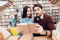 Ethnic asian girl and white guy surrounded by books in library. Students are reading book. Ethnic asian girl and white guy sitting at table surrounded by books Royalty Free Stock Photos