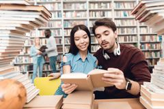 Ethnic asian girl and white guy surrounded by books in library. Students are reading book. Ethnic asian girl and white guy sitting at table surrounded by books Stock Photos