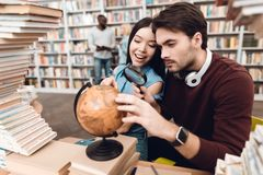 Ethnic asian girl and white guy surrounded by books in library. Students are using globe. royalty free stock image