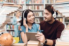 Ethnic asian girl and white guy surrounded by books in library. Students are using tablet with headphones. stock image