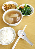 Ethnic asian meal. A photograph of a southeast asian chinese meal of steamed white rice, served with pork bone soup of bak kut teh, green stir fried vegetables Stock Photography