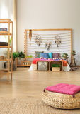 Bedroom with shelves and ottoman. Ethnic bedroom with wooden shelves and wicker ottoman Royalty Free Stock Image