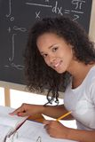 Ethnic black college student studying math exam. High school or college African-American black female student sitting by the desk at math class. Blackboard with Stock Photos