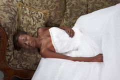 Ethnic black woman bride wedding dress on couch Royalty Free Stock Photo