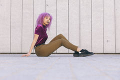 Ethnic black woman standing on the floor isolated on a grey wall. Ethnic black woman with purple afro hair standing on the floor isolated on a grey wall Royalty Free Stock Photos