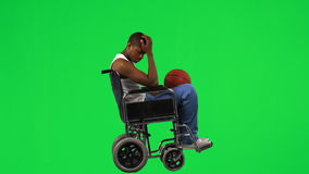 Ethnic boy on a wheelchair playing with a basket ball stock video footage
